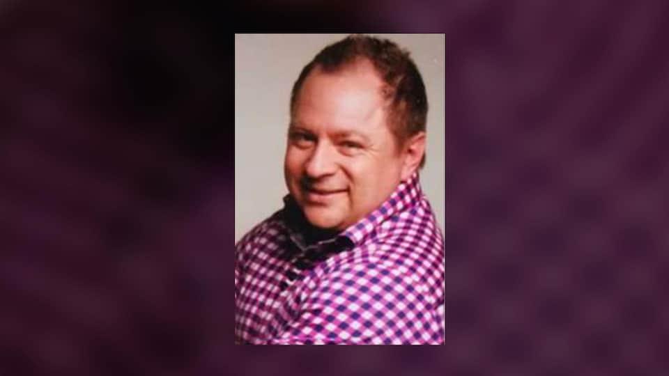 Photo de Michel Mercier, un homme aux cheveux bruns et qui porte une chemise à carreaux rose, mauve et blance.