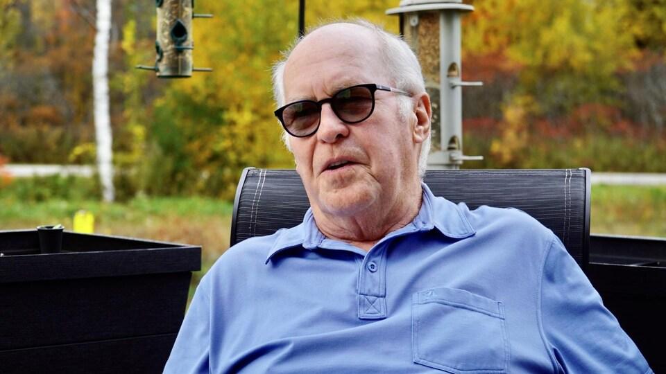 Michel Monfette est assis dans sa cour. Il porte des lunettes de soleil.