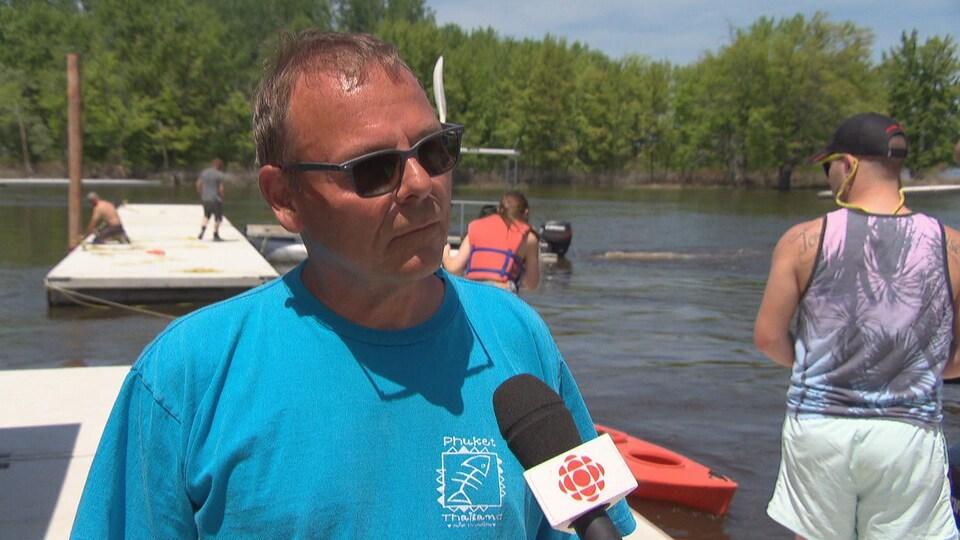 Un homme en entrevue sur un quai. Derrière, une femme s'apprête à embarquer dans son kayak.