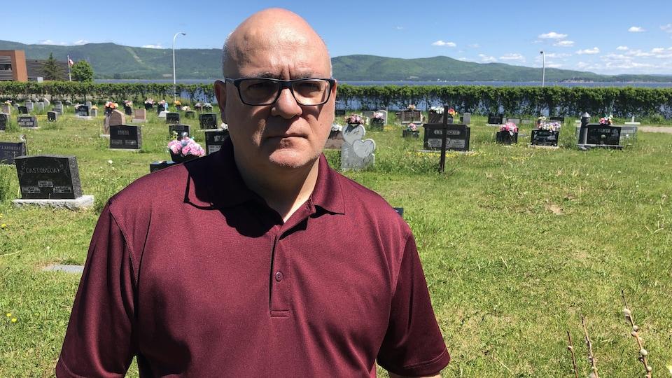 Homme chauve avec lunettes et gilet bourgogne, pose dans un cimetière.