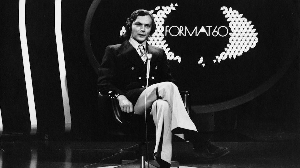 Dans un studio de télévision, l'animateur Michel Pelland est assis sur un fauteuil et derrière lui un écran affiche le titre de l'émission.