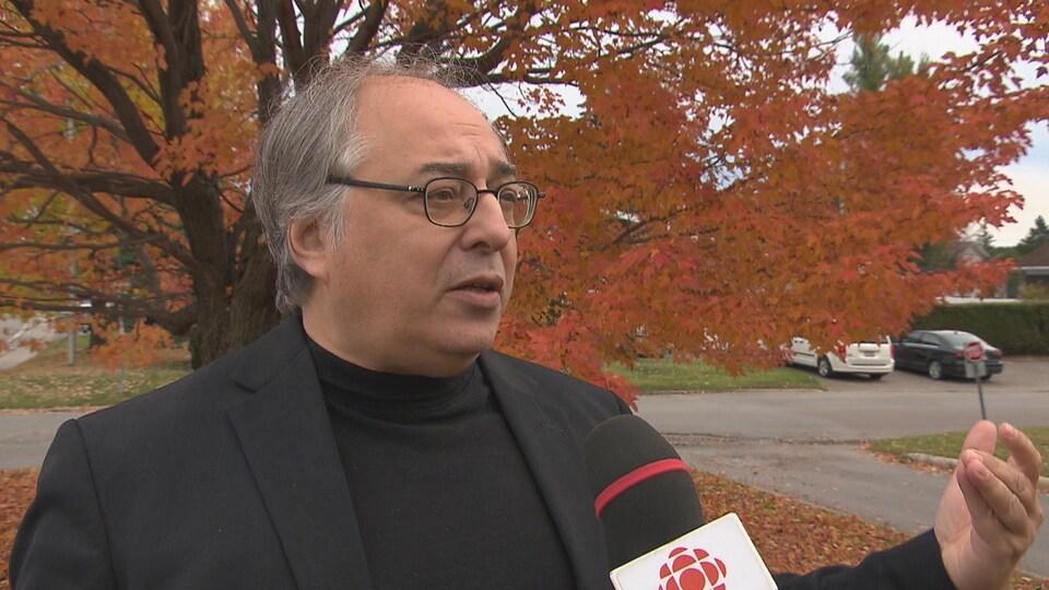 Michel Roche en entrevue à l'extérieur, devant un érable