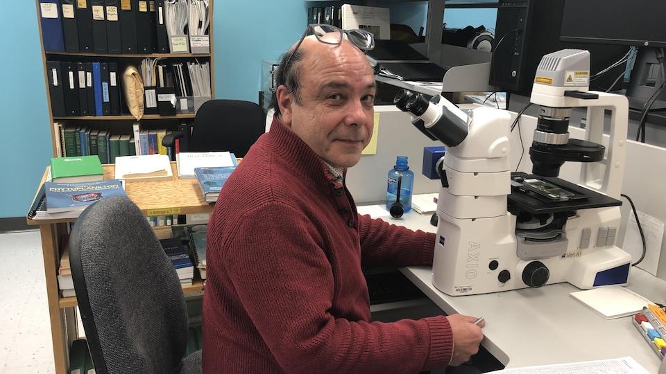 Michel Starr devant un microscope.