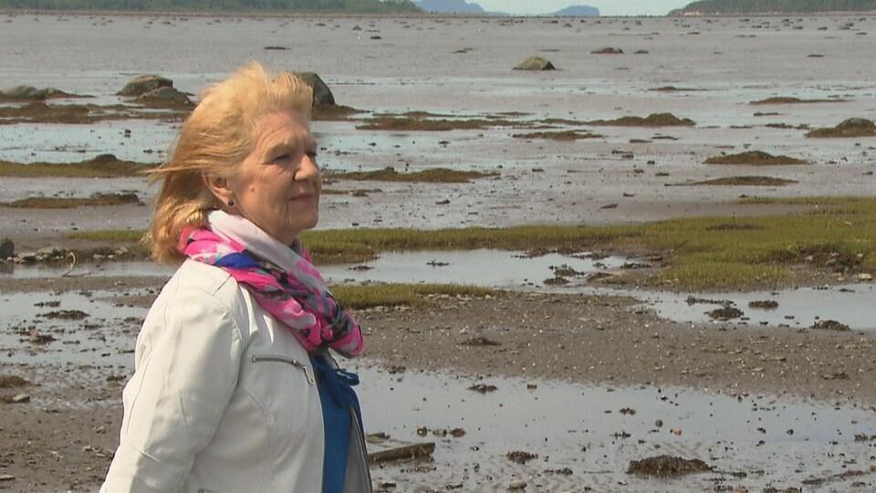 Un femme regarde vers l'horizon aux abords du fleuve Saint-Laurent.