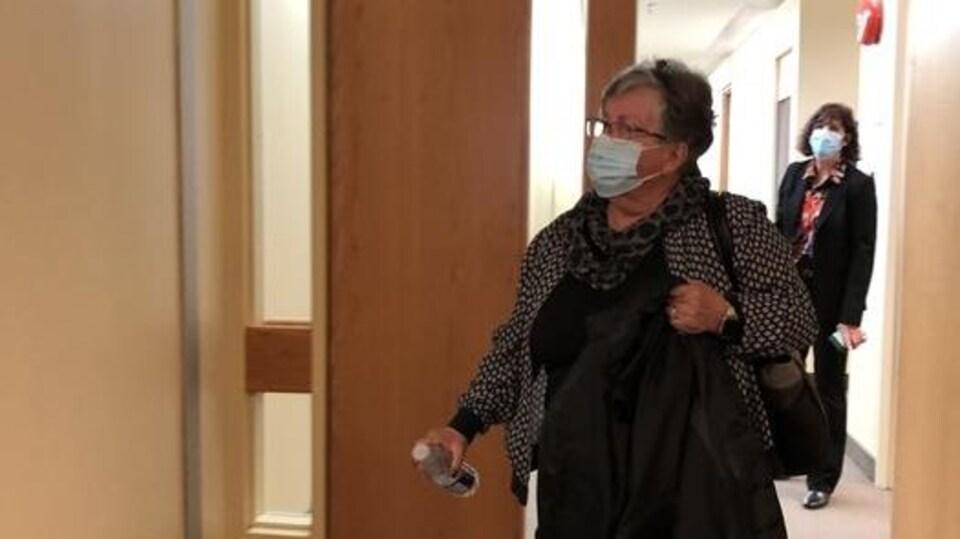 Une femme marche dans un corridor.