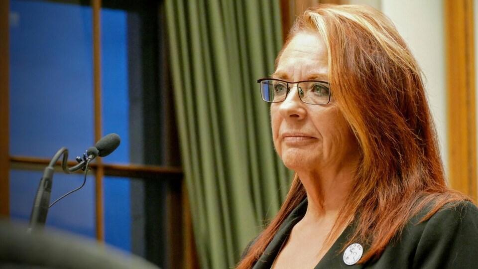 Une femme au cheveux longs roux se tient devant un micro.
