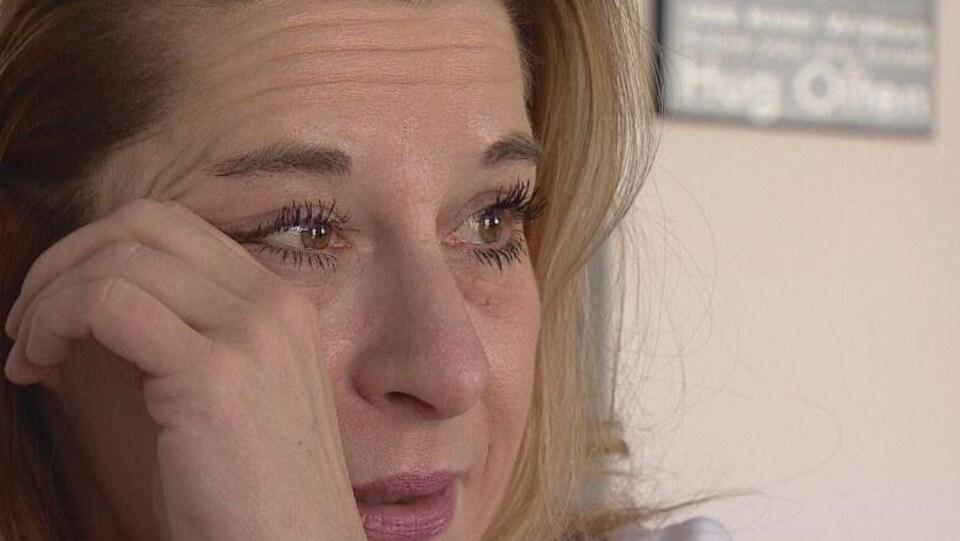 Plan serré du visage de Michelle Straschnitzki essuyant une larme.