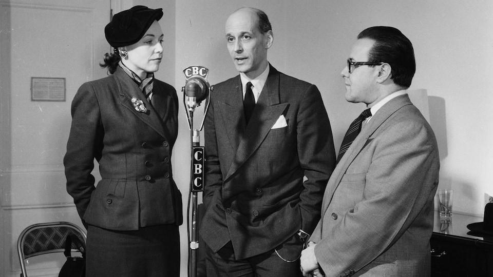 L'animatrice Michelle Tisseyre, Rudolf Bing et Noël Gauvin sont debout autour d'un micro sur pied.