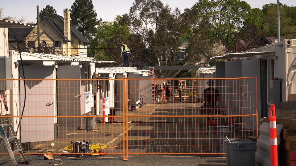 Des travailleurs s'affairent derrière une clôture en grille qui barre le passage.