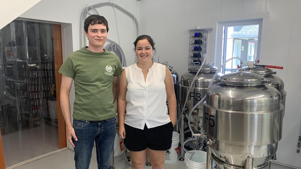 Un homme et une femme posent dans les installations de sa microbrasserie.