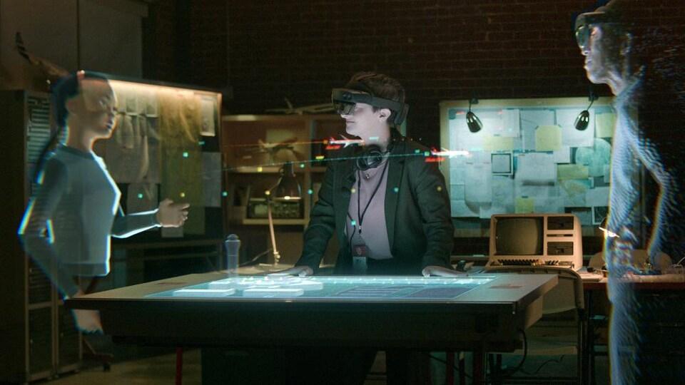 Deux hologrammes sont autour d'une table avec une personne portant un casque.