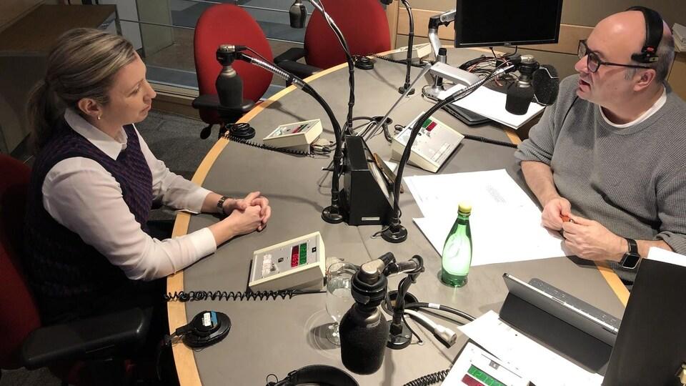 Une femme et un homme assis dans un studio de radio devant des micros.