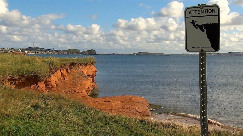 Sur une berge des Îles-de-la-Madeleine, on voit l'érosion sur le bord d'une petite falaise. En avant-plan, une affiche signale les dangers de ce phénomène.