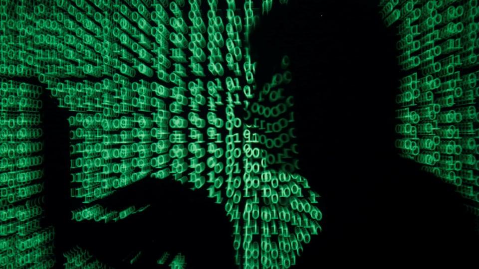 L'ombre stylisée d'un jeune homme face à un ordinateur portable