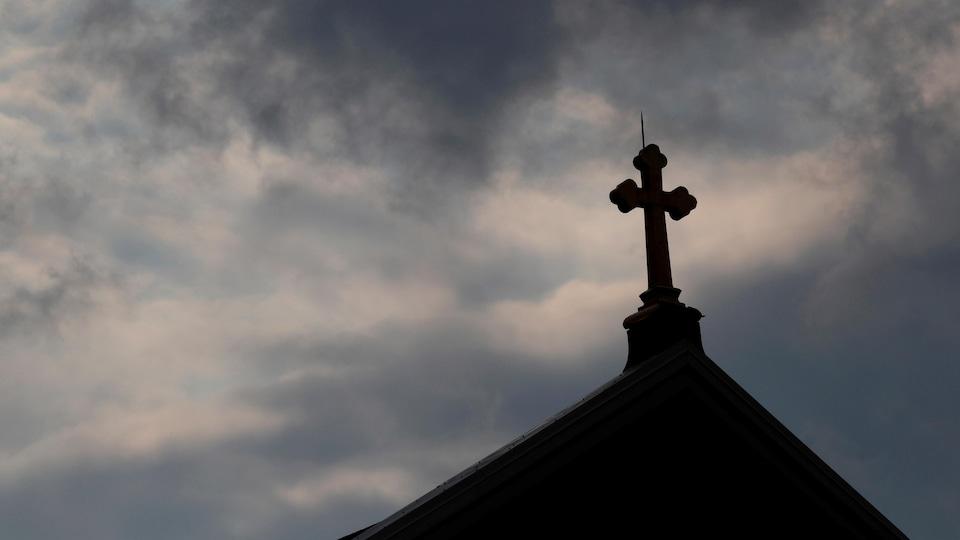 Des nuages noirs se glissent à l'arrière-plan d'une croix sur le toit d'une église catholique.