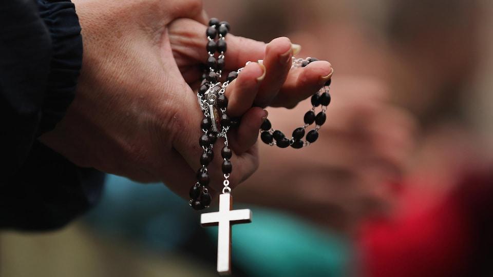 Les mains jointes, une paroissienne tient un chapelet avec, au bout, une croix bien visible au bout de la chaîne.