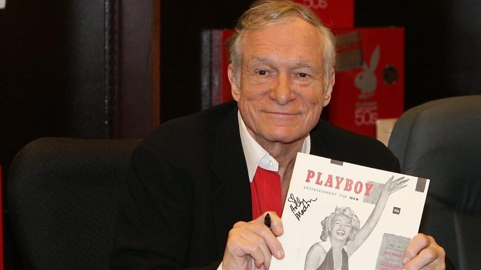 Le fondateur de la revue Playboy, Hugh Hefner, montre un numéro d'archives.