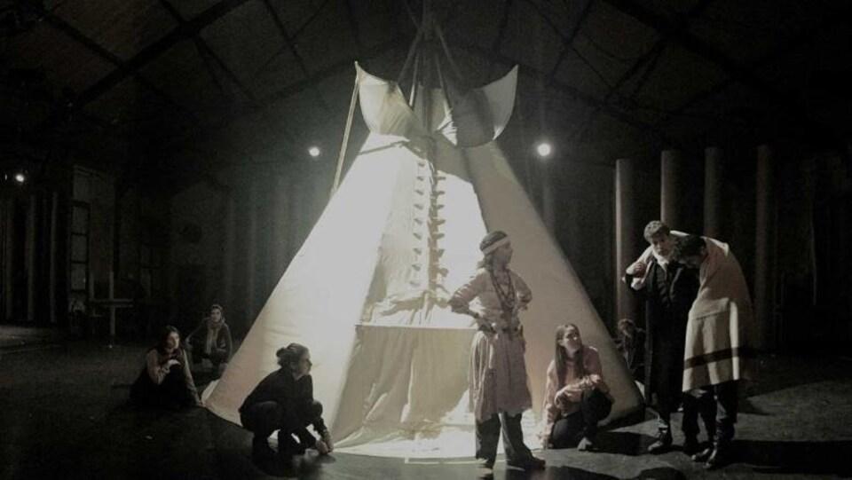 Des acteurs déguisés en Autochtones sont devant un tipi sur une scène.