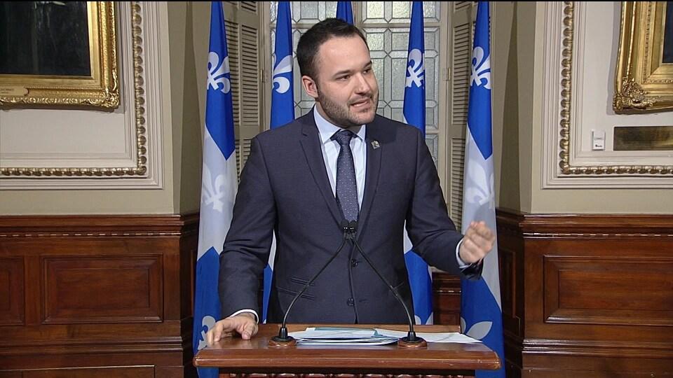 Mathieu Lacombe s'adresse aux journalistes à un podium, devant des drapeaux du Québec.