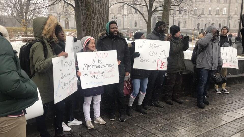 Les manifestants avec leurs pancartes, devant l'assemblée nationale