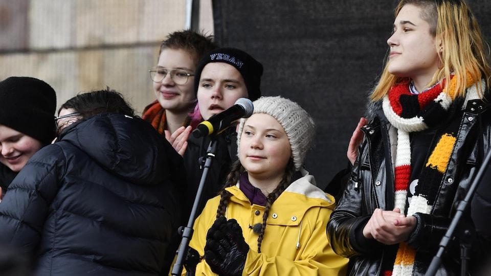 La militante Greta Thunberg devant un micro et des manifestants.
