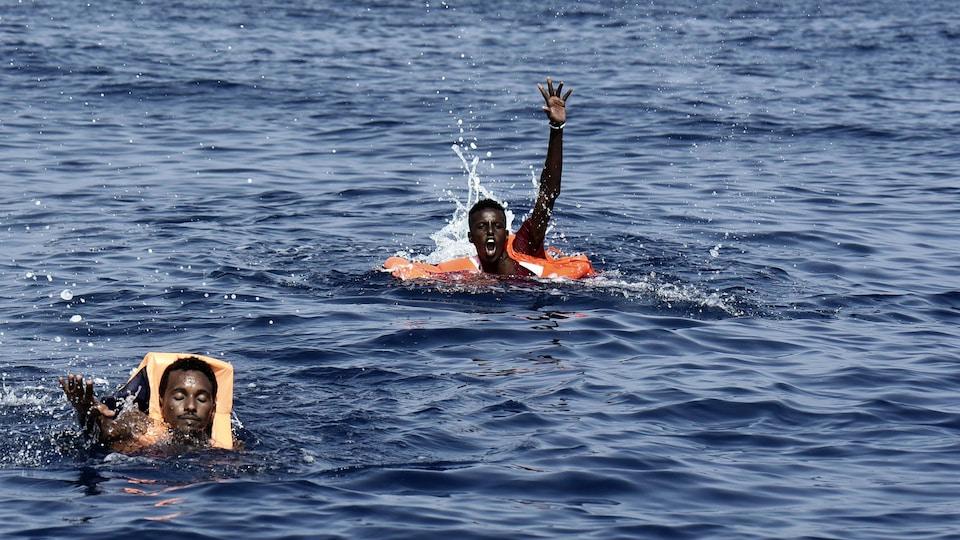 Deux hommes en mer, dont un lève la main appelant au secours.