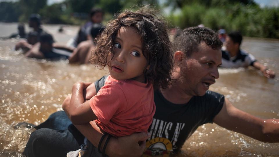 Un homme d'une caravane de migrants d'Amérique centrale en route vers les États-Unis, porte une jeune fille en traversant le fleuve Suchiate jusqu'au Mexique.