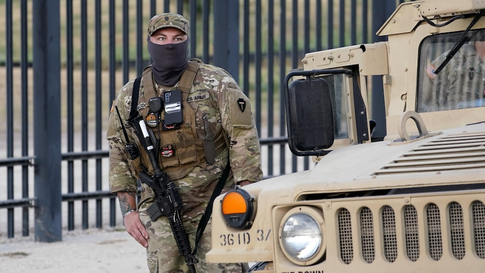 Un militaire américain, armé d'un fusil d'assaut, se tient debout près d'un véhicule.