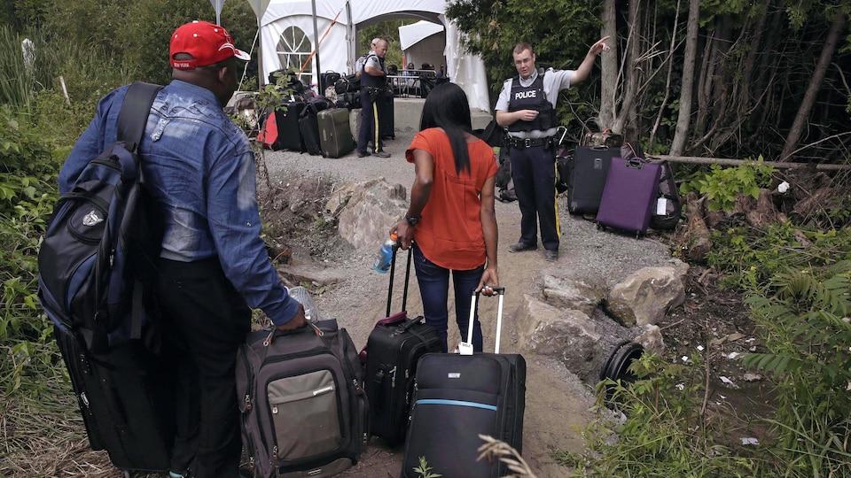 Un agent de la GRC parle à des gens qui arrivent à la frontière avec leur valise.