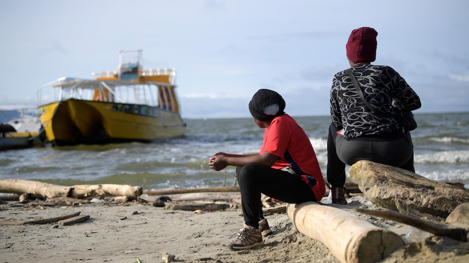 Two people are sitting in the sea.