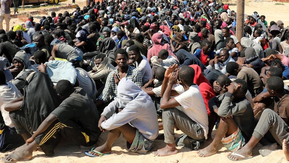 Des centaines d'hommes sont assis par terre dans le sable en rang serré.