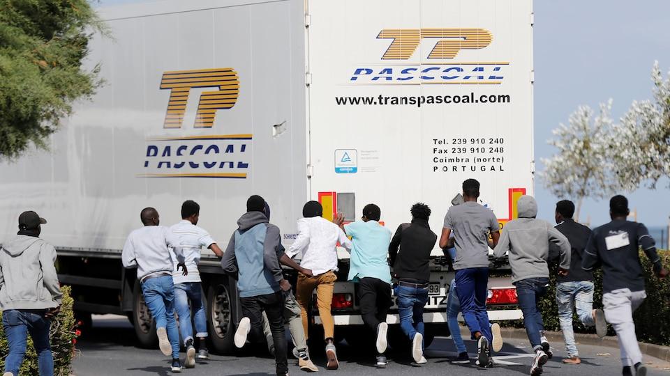 Une dizaine de migrants courent derrière un camion de marchandise.