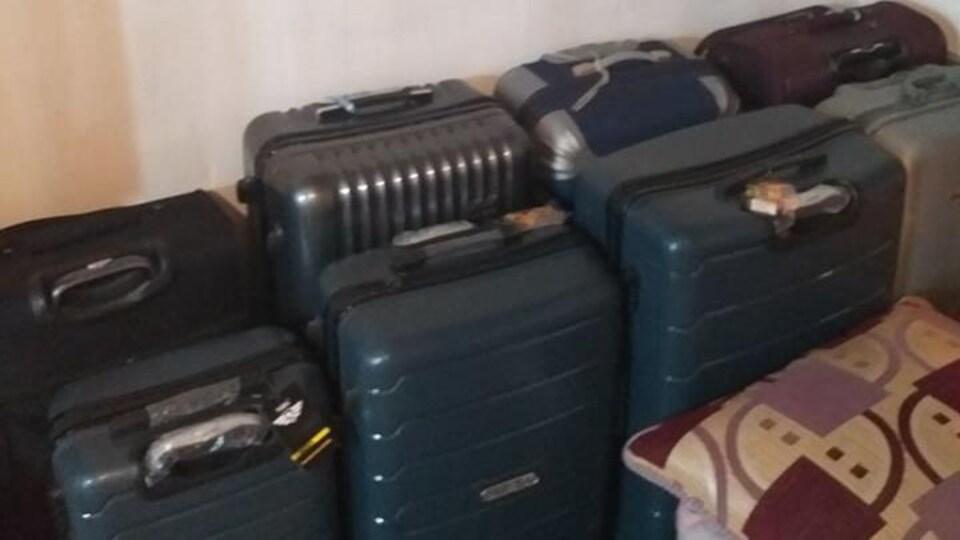 8 valises alignées dans une pièce exiguë.
