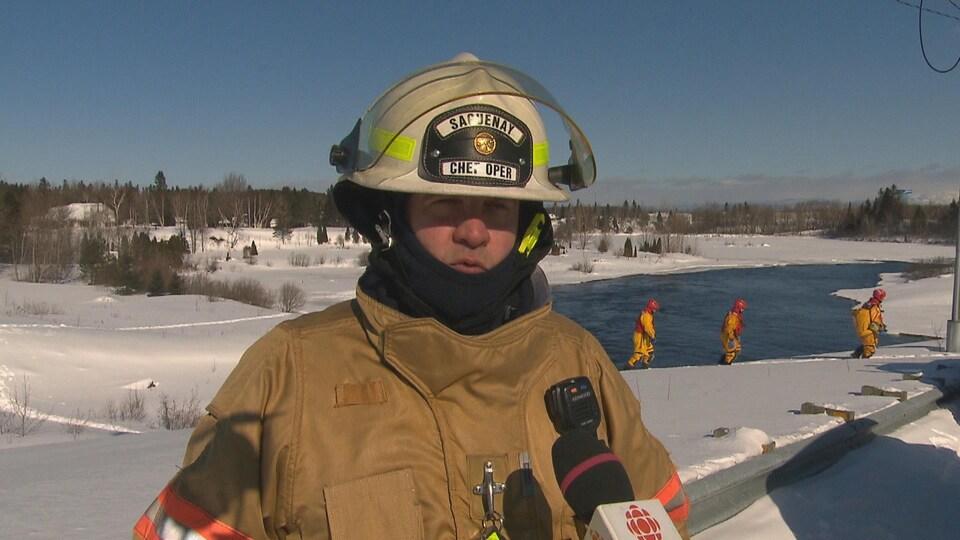 Un pompier en entrevue à Radio-Canada. On voit trois pompiers qui marchent derrière lui.