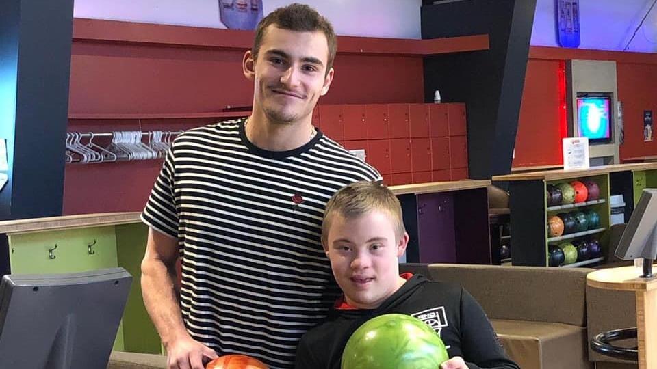 Mikael Martel pose avec Ely, un jeune homme qui vit avec la trisomie 21.