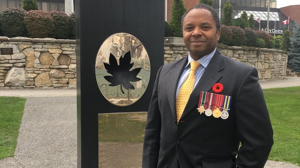Portrait d'un homme en costume. Il porte une barette de médailles. Il est debout devant un monument qui arbore une feuille d'érable stylisé et une plaque dorée portant des inscriptions illisibles