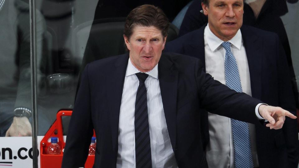 L'entraîneur-chef des Maple Leafs, Mike Babcock, dirige son équipe depuis le banc des joueurs.