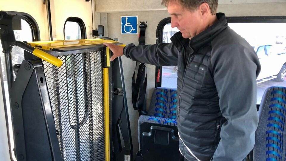 Mike Cassidy montre un ascenseur à l'intérieur d'un autobus adapté.