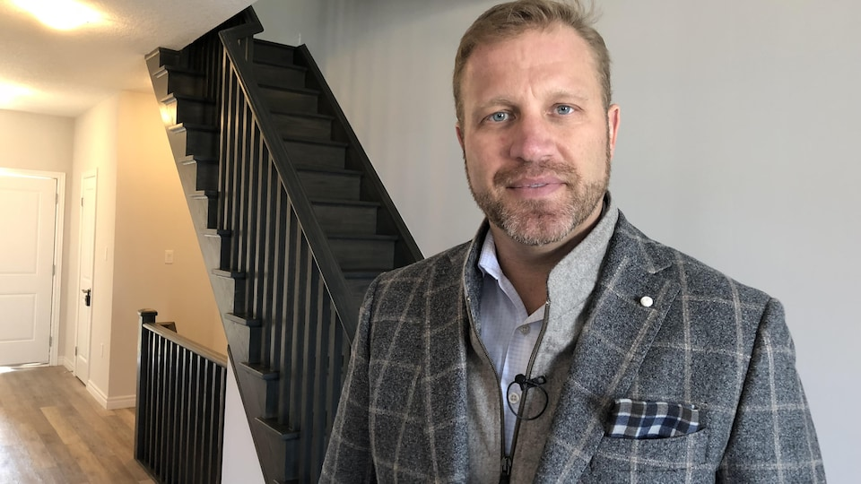 Un homme en costume se tient devant l'escalier d'une maison à vendre.