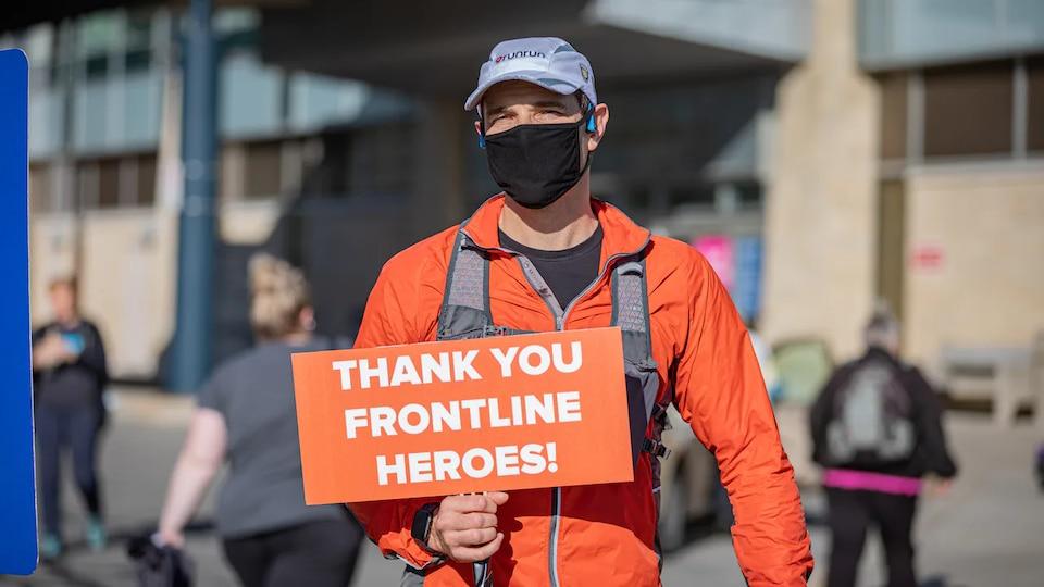 Le coureur tient dans sa main un affiche sur laquelle il est écrit, en anglais, « Merci aux travailleurs de première ligne, des héros ».