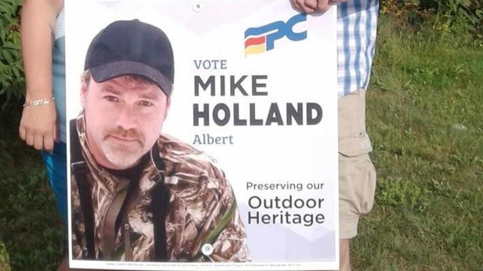 Deux personnes hors champs tiennent une affiche électorale de Mike Holland.