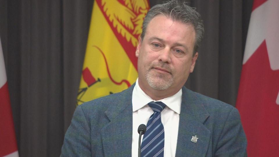 Mike Holland devant les drapeaux du Nouveau-Brunswick et du Canada.