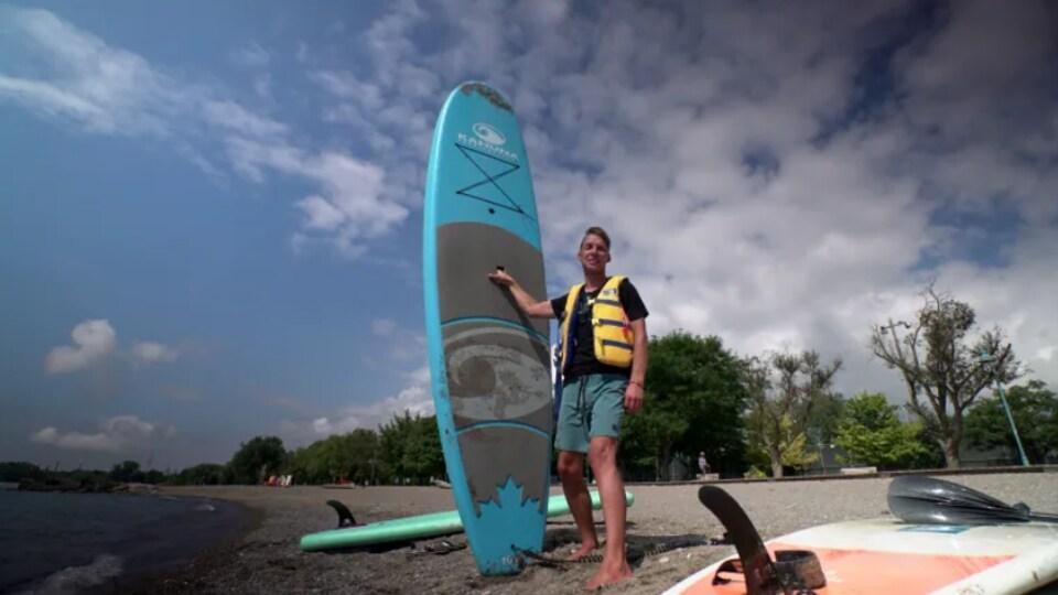Mike Shoreman se situe sur la plage avec une planche à pagaie.