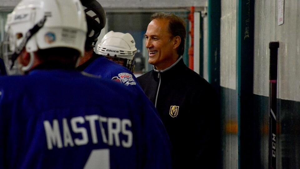 Mike Foligno se tient debout derrière un banc des joueurs de hockey dans une aréna.