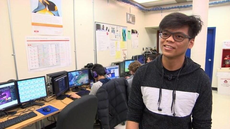 Un jeune homme porte des lunettes et un chandail bleu et blanc, photographié dans une salle de classe.