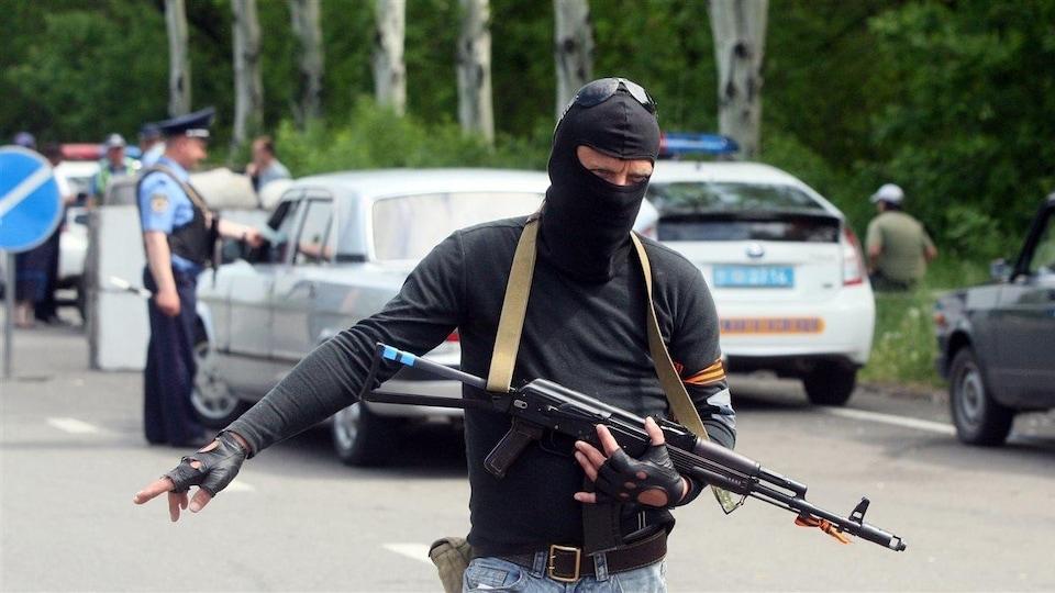 Un homme armé et cagoulé à un poste de contrôle routier.