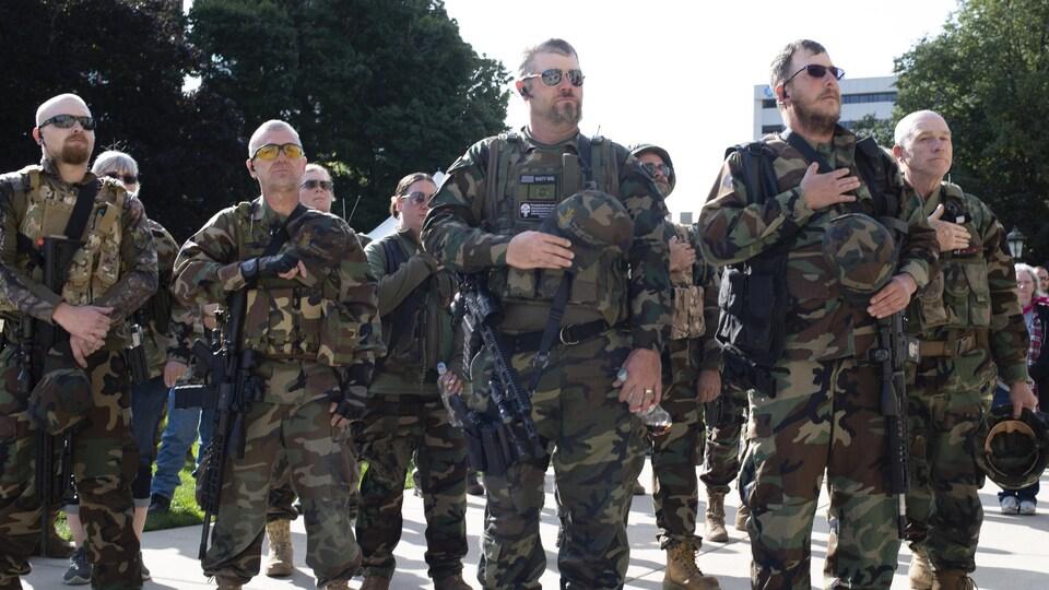 Des hommes armés en tenues militaires écoutent l'hymne national américain.