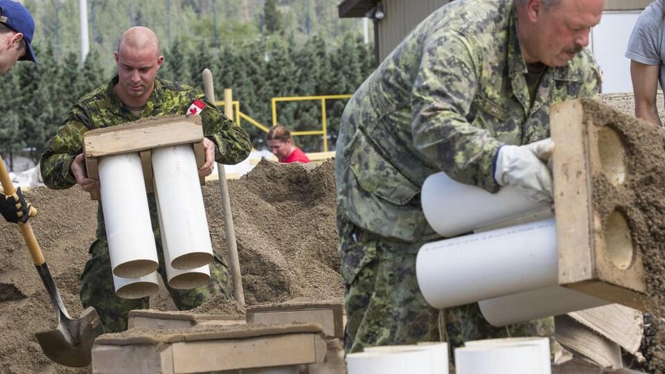 Des militaires s'activent à contruire une digue avec des poches de sable et du matériel de retenue pour contrer la crue des eaux à Grand Forks en Colombie-Britannique.
