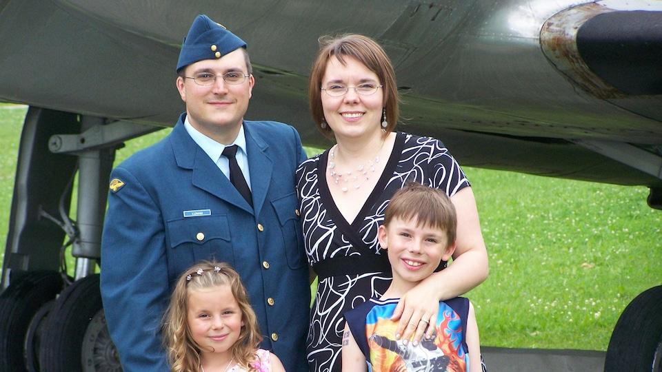 Un militaire en uniforme bleu pose avec sa famille.