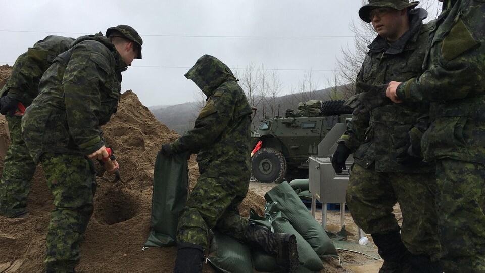 Cinq militaires remplissent des sacs de sable.